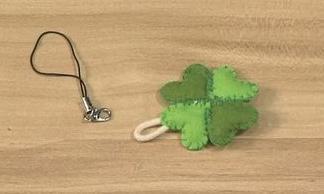 将四个心形缝合在一起,形成四叶草的形状。 在露出来的麻绳处装上龙虾扣。 一个漂亮的四叶草手机链就做好了